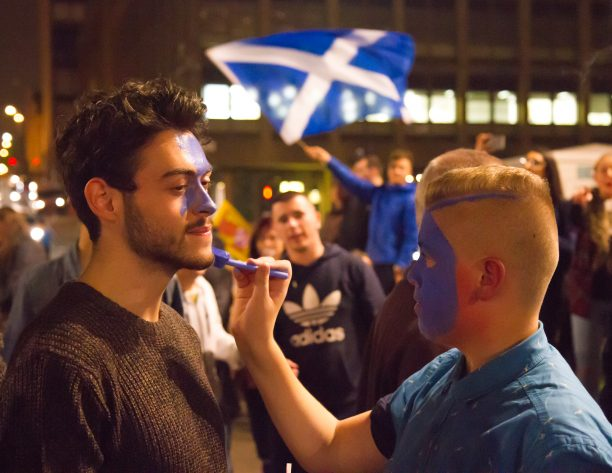 Someone applying face paint to someone else with a saltire in the background